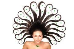 le brunet a décoré les pierres vertes de cheveu de filles image stock