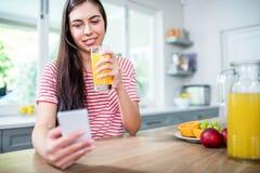 Le brunett genom att använda smartphonen och att dricka orange fruktsaft royaltyfri bild