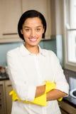 Le brunett med armar korsade bärande gula handskar Arkivfoto