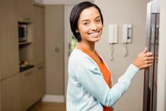 Le brunett med handen på kylskåpet Royaltyfri Fotografi