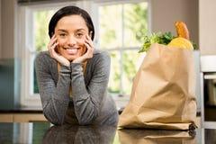 Le brunett med livsmedelsbutikpåsen på räknare Royaltyfri Foto