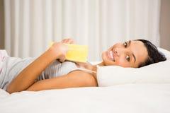 Le brunett på säng med boken Royaltyfri Foto