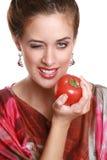 Le brunette à la mode avec une tomate dans des mains image stock