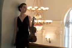 Le brunette de beauté joue le violon photographie stock libre de droits
