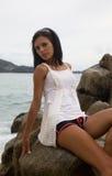 Le brunette mince s'assied sur une roche par la mer Photo stock