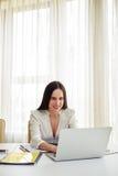 Le brunetten som arbetar på hennes vita bärbar dator Royaltyfri Fotografi