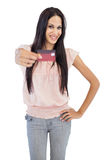 Le brunetten som visar hennes kreditkort till kameran Royaltyfri Foto