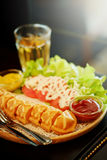 Le bâton de hot-dog de gaufre a placé avec de la salade et le thé chaud sur la table Images libres de droits