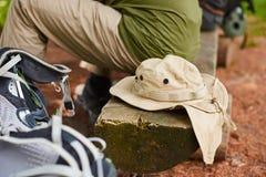 Le bugie turistiche del cappello accanto agli uomini si siede sul ceppo Immagini Stock Libere da Diritti