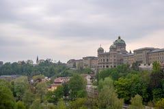 Le Bundeshaus avec le premier plan vert d'arbres et le fond de ciel nuageux images stock