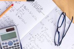 Le bureau avec des verres de calculatrice parque le livre d'exercice de travail de maths images stock