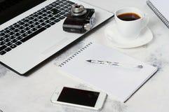Le bureau avec l'ordinateur, le téléphone, l'appareil-photo, la tasse de café et la pivoine fleurit Pause-café, idées, notes ou p Photographie stock libre de droits