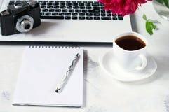 Le bureau avec l'ordinateur, le téléphone, l'appareil-photo, la tasse de café et la pivoine fleurit Pause-café, idées, notes ou p Image libre de droits