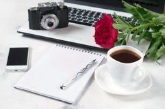 Le bureau avec l'ordinateur, le téléphone, l'appareil-photo, la tasse de café et la pivoine fleurit Pause-café, idées, notes ou p Photo stock