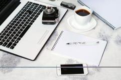 Le bureau avec l'ordinateur, le téléphone, l'appareil-photo, la tasse de café et la pivoine fleurit Pause-café, idées, notes ou p Photographie stock