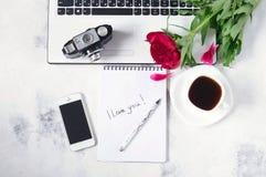 Le bureau avec l'ordinateur, le téléphone, l'appareil-photo, la tasse de café et la pivoine fleurit Pause-café, idées, notes ou p Photo libre de droits