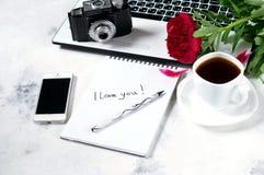 Le bureau avec l'ordinateur, le téléphone, l'appareil-photo, la tasse de café et la pivoine fleurit Pause-café, idées, notes ou p Images stock