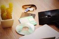 Le bureau avec la note, l'A à disque souple, le B à disque souple et la mémoire conduisent dans le siège social, le bureau privé  Photographie stock libre de droits