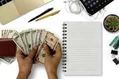 Le bureau blanc avec des dollars US comptent, smartphone avec le noir Photo stock