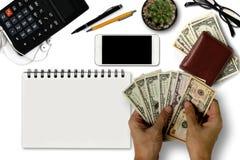 Le bureau blanc avec des dollars US comptent, smartphone avec le noir Images libres de droits