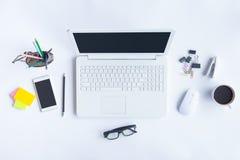 Le bureau blanc de bureau avec l'ordinateur portable, le smartphone et autre fonctionnent le supplie Photos libres de droits
