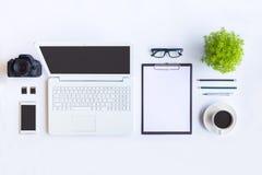 Le bureau blanc de bureau avec l'ordinateur portable, le smartphone et autre fonctionnent le supplie Photos stock