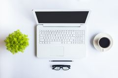 Le bureau blanc de bureau avec l'ordinateur portable, le smartphone et autre fonctionnent le supplie Photographie stock libre de droits