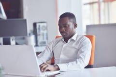 Le bureau d'At Computer In d'homme d'affaires de créent des affaires Photographie stock