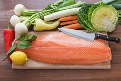 Le bureau de cuisine avec le filet saumoné est entouré par le veget frais Image stock