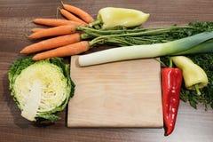 Le bureau de cuisine est entouré par les légumes frais Photos stock