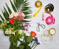 Le bureau de fleuriste avec des outils de travail sur le fond en bois images stock