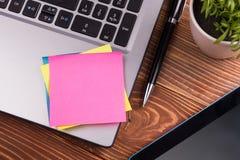 Le bureau de table de bureau avec des approvisionnements, bloc-notes vide blanc, tasse, stylo, PC, a chiffonné le papier, fleur s Photo libre de droits