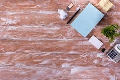 Le bureau de table de bureau avec des approvisionnements, bloc-notes vide blanc, tasse, stylo, PC, a chiffonné le papier, fleur s Image libre de droits
