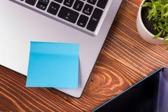 Le bureau de table de bureau avec des approvisionnements, bloc-notes vide blanc, tasse, stylo, PC, a chiffonné le papier, fleur s Photographie stock libre de droits