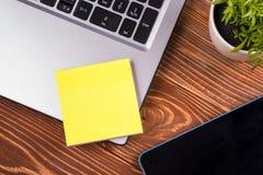 Le bureau de table de bureau avec des approvisionnements, bloc-notes vide blanc, tasse, stylo, PC, a chiffonné le papier, fleur s Image stock