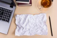 Le bureau de table de bureau avec des approvisionnements, bloc-notes vide blanc, tasse, stylo, PC, a chiffonné le papier, fleur s Photos libres de droits