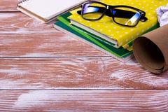 Le bureau de table de bureau avec des approvisionnements, bloc-notes vide blanc, tasse, stylo, PC, a chiffonné le papier, fleur s Photos stock