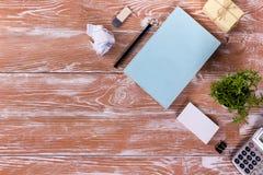Le bureau de table de bureau avec des approvisionnements, bloc-notes vide blanc, tasse, stylo, PC, a chiffonné le papier, fleur s Photographie stock