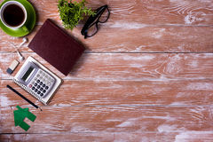 Le bureau de table de bureau avec des approvisionnements, bloc-notes vide blanc, tasse, stylo, PC, a chiffonné le papier, fleur s Photo stock