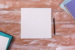 Le bureau de table de bureau avec des approvisionnements, bloc-notes vide blanc, tasse, stylo, PC, a chiffonné le papier, fleur s Images stock