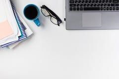 Le bureau de table de bureau avec des approvisionnements, bloc-notes vide, tasse, stylo, PC, a chiffonné le papier, fleur sur le  Images libres de droits