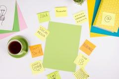 Le bureau de table de bureau avec des approvisionnements de vert, bloc-notes vide, tasse, stylo, verres, a chiffonné le papier, l Photo libre de droits
