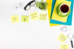 Le bureau de table de bureau avec des approvisionnements de vert, bloc-notes vide, tasse, stylo, verres, a chiffonné le papier, l Photos stock