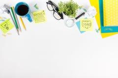 Le bureau de table de bureau avec des approvisionnements de vert, bloc-notes vide, tasse, stylo, verres, a chiffonné le papier, l Photo stock