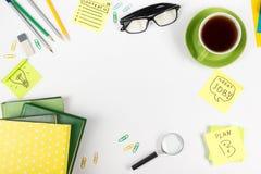 Le bureau de table de bureau avec des approvisionnements de vert, bloc-notes vide, tasse, stylo, verres, a chiffonné le papier, l Image stock