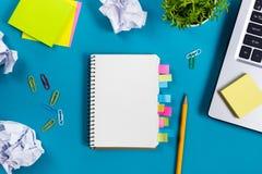 Le bureau de table de bureau avec l'ensemble d'approvisionnements colorés, bloc-notes vide blanc, tasse, stylo, PC, a chiffonné l Images stock