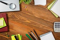 Le bureau de table de bureau avec l'ensemble d'approvisionnements colorés, bloc-notes vide blanc, tasse, stylo, PC, a chiffonné l Image libre de droits