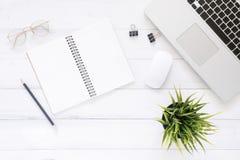 Le bureau de vue supérieure avec l'ordinateur portable, raillent vers le haut des carnets et de l'usine sur le fond en bois blanc Image libre de droits