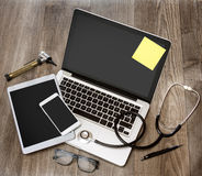 Le bureau du docteur en bois dans la définition élevée avec l'ordinateur portable, le comprimé et le MOIS Photographie stock