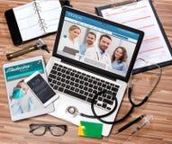 Le bureau du docteur en bois dans la définition élevée avec l'ordinateur portable, le comprimé et le MOIS Photos libres de droits